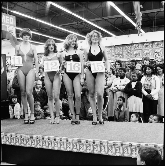 David Goldblatt, Saturday morning at the Hypermarket: Miss Lovely LegsCompetition,1980; gelatin silver print; 11 x 11 in. (28 x 28 cm);Courtesy of the artist and Goodman Gallery, South Africa; © DavidGoldblatt
